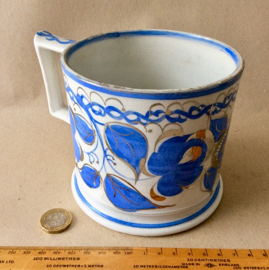 Antique Victorian pottery mug with hand painted decoration with blue flowers and silver resist highlights.
