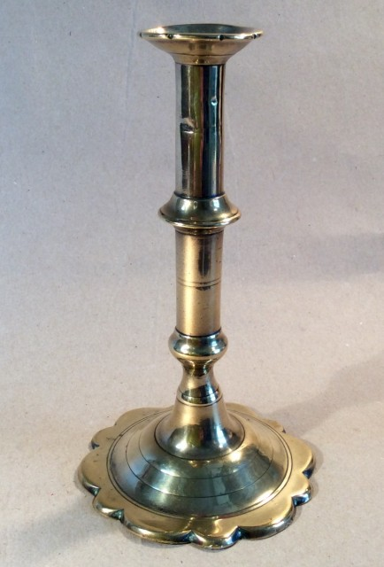 Single 18th century brass candle stick with petal base