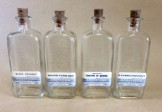 Four glass medicine bottles with chemist labels