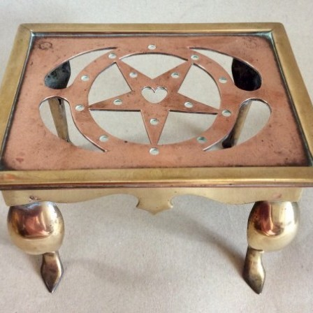 Detail: Small late Victorian/Edwardian pierced copper and brass Footman or Trivet.