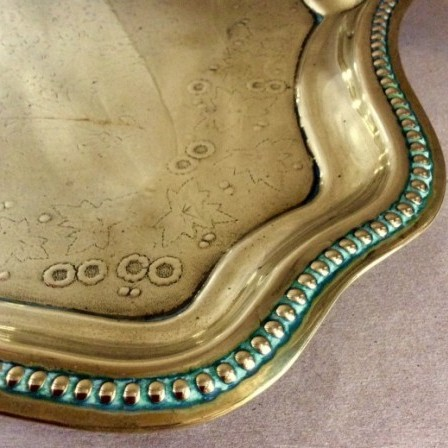 Detail: Victorian pressed brass tray with wavy edge an flower decoration to centre.