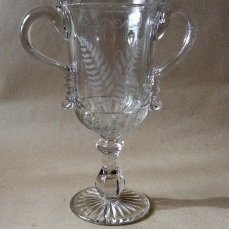 Detail: Antique clear pressed and engraved  glass Celery vase  with applied strap handles (trophy shape)